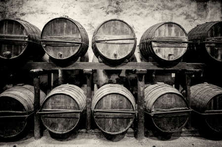 Barrels stacked in the winery in black and white