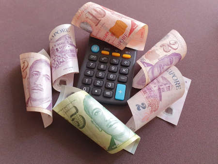 Photo for calculator and singaporean banknotes of different denominations - Royalty Free Image