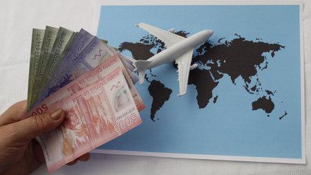 Foto de hand holding Chilean money and figure of an airplane on a world map - Imagen libre de derechos