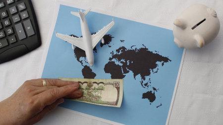 Foto de hand holding Nepalese money and figure of an airplane on a world map - Imagen libre de derechos