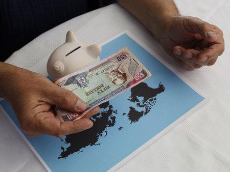 Foto de hand holding Jamaican money and piggy bank on a world map - Imagen libre de derechos