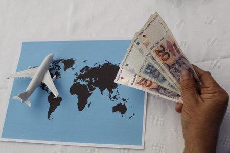 Foto de hand holding Croatian money and figure of an airplane on world map - Imagen libre de derechos