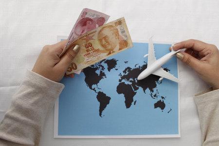 Foto de hand holding turkish money and plastic airplane figure on a world map - Imagen libre de derechos