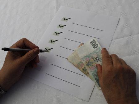 Foto de hands of a woman holding czech banknotes, with a list of goals on the table - Imagen libre de derechos