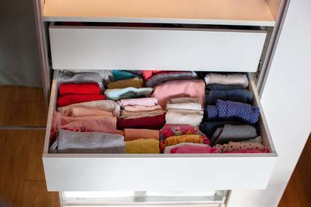 Photo pour Vertical storage of clothing. Clothing folded for vertical storage in the linen drawer. Nursery. Sliding wardrobe. Room interior. Neatly folded clothes in chest of drawers. - image libre de droit