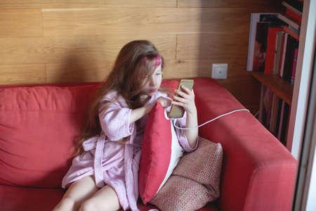 Foto de A seven-year-old girl sits on a sofa in a bathrobe and watches a cartoon on the phone. - Imagen libre de derechos