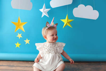 Photo pour One year old baby celebrates birthday. Photo zone. Cute dress in white color. She touches a paper yellow star. - image libre de droit
