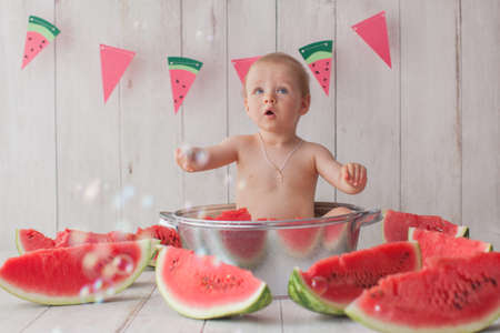 Photo pour One year old baby girl takes a bath with watermelon. Paper flag garland on background. - image libre de droit