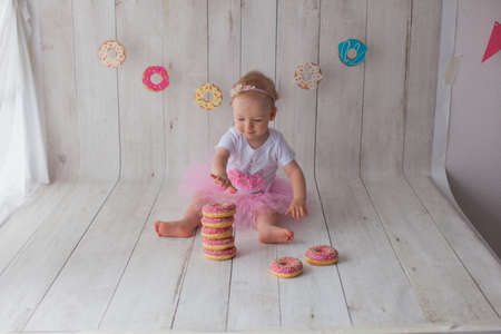 Photo pour One year old baby girl celebrates her birthday. Doughnut background. Handmade paper cutout garland. - image libre de droit