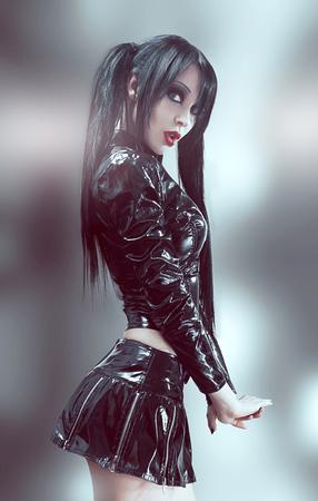 Gothic studio portrait of brunette sexy woman in black vinyl costume