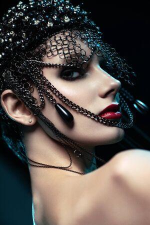 Photo pour Portrait of attractive brunette woman in designer headdress with chains posing on dark studio background - image libre de droit