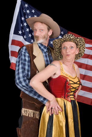 Senior married American couple in traditional cowboy Western outfit posing and backed by the stars and stripes flag.の写真素材