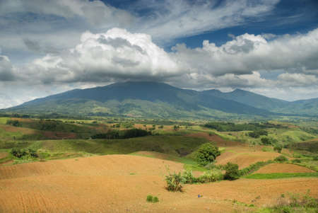 Plowed field with rich fertile soil on a volcanic tropical plateau in front of a mountain covered with rain forest and topped by a majestic cloudscape with nimbus clouds around mountain top in Bukidnon (Mindanao, Philippines).