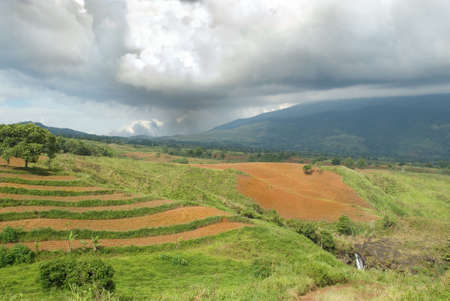 Tropical agriculture landscape with plowed fields under a low nimbus cloudscape on the Bukidnon (Mindanao, Philippines) volcanic mountainous plateau with red fertile volcanic soil, jungle and canyons.