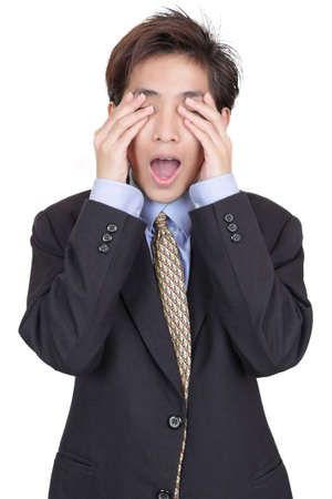Standing oriental Chinese young businessman covering his eyes in denial of reality and blinded for corporate and business challenges. Isolated over white.