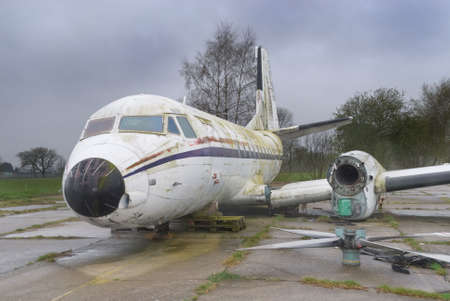 Decommissioned but intact vintage wrecked airplane with detached wings and propeller engines laying on a lone strip.