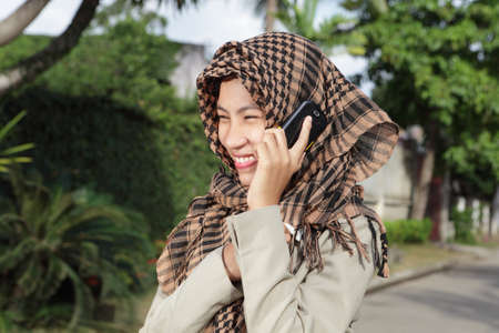 Attractively laughing happy Asian Muslim girl with headscarf or hijab and in formal jacket calling by cell phone outside on a tropical affluent residential street.