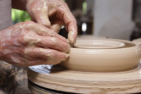 Photo pour Cropped close-up of potter's hands shaping clay on a turning wheel into kitchenware plate in an Asian Philippines pottery. - image libre de droit