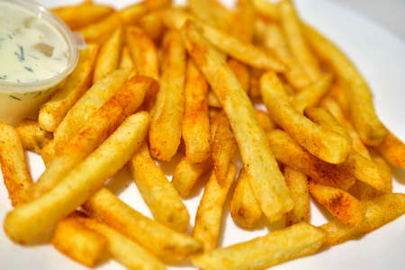 Photo for Bright yellow French fries on a white plate with sauce - Royalty Free Image