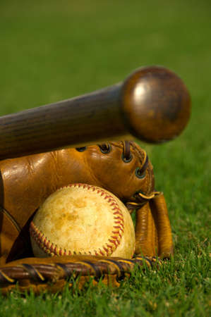 Vintage baseball with bat and glove on grass fieldの写真素材