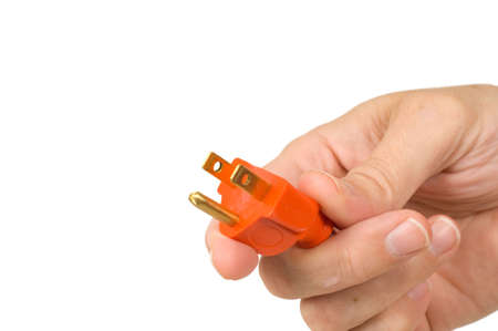 A man's hand holding the end of a new orange extension cord on a white background, symbol for connection or getting connected or plugged in