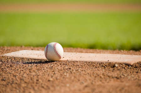A white leather baseball lying on top of the pitchers mound at a baseball field with copy s