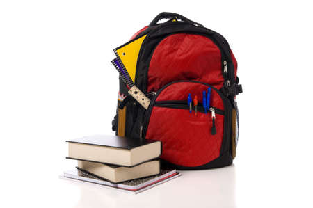A red overflowing school backpack  or book bag with school books on a white background