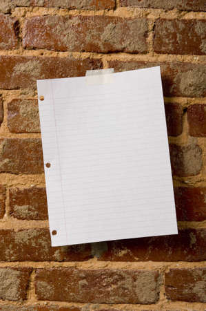 A blank sheet of paper taped to a brick wall with copy space