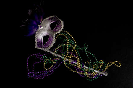 A Mardi Gras or constume party mask with beads on a black background