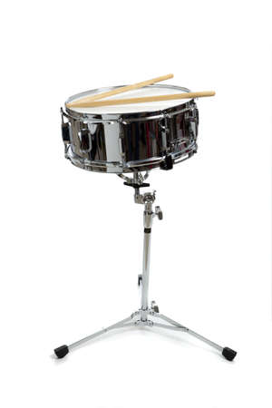 A snare drum on stand on a white background with drumsticks.  Percussion Instrument