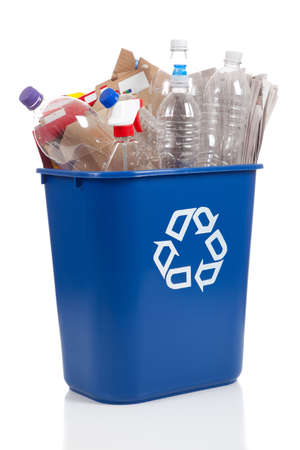 An overflowing blue recycle bin full of  plastic bottles, newspapers and boxes, with the recyle symbol on front
