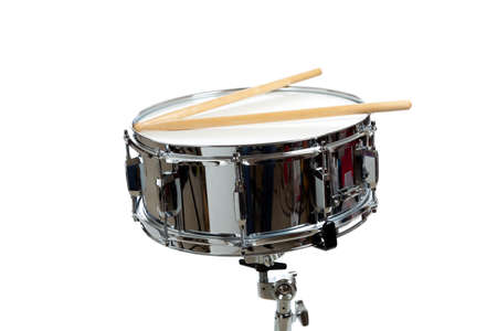 A snare drum with drum sticks on a white background