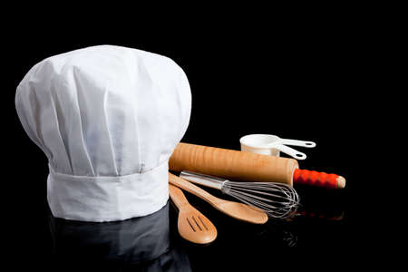 Photo pour A white toque with cooking utensils including rolling pin, wooden spoons, wisk and measuring cups on a black background - image libre de droit