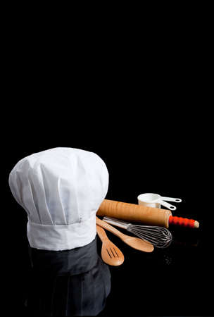 Photo pour A chef's toque with kitchen utensils including wooden spoons, rolling pin, wire whisk and measuring cups on a black background - image libre de droit