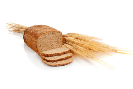 A loaf of wheat bread and shock of wheat on a white background