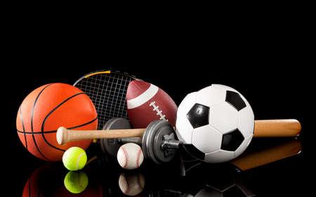 Assorted sports equipment including a basketball, soccer ball, tennis ball, baseball, bat, tennis racket, football and dumbbells on a black background
