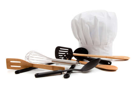 A white chef's toque with various cooking utensils including a wisk, wooden spoons, spatulas on a white background