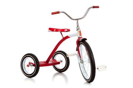 A child's red tricycle on a white background
