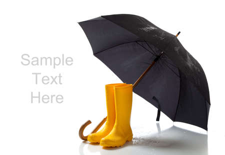 A pair of yellow rainboots and a black umbrella on a white background with copy space