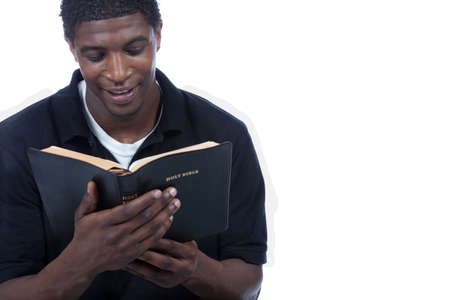 A young black man reading the Holy Bible on a white background
