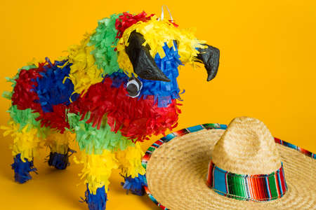 A mexican torro pinata and sombrero on a yellow background