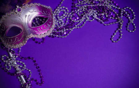 A purple mardi gras mask on a purple background with beads.  Carnivale costume.