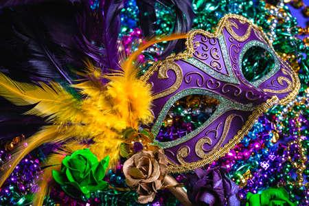 Photo pour Colorful Mardi Gras mask on purple background with beads - image libre de droit