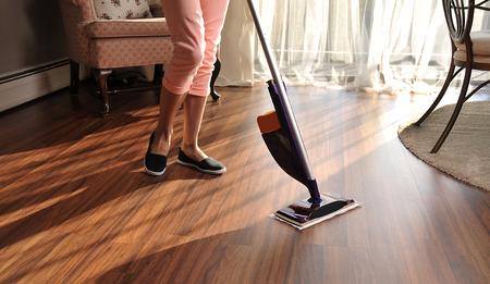Foto de Modern mop for cleaning wooden floor from dust, cleaning service - Imagen libre de derechos