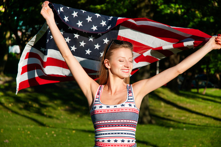 Young happy patriot girl holding the american, united states flag