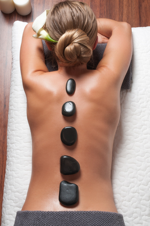 Foto de Beauty treatments woman getting spa on a stone therapy, hot stone massage. Girl resting at spa salon on vacation - Imagen libre de derechos