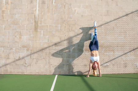 Foto de Healthy lifestyle and yoga concepts. Fitness woman in sportswear is doing exercise, stretches on the wall - Imagen libre de derechos