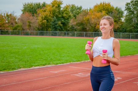 Photo pour Healthy lifestyle and diet concept. Woman runner with dumbbells is running outdoor - image libre de droit