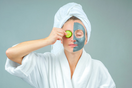 Spa Clay Mask. Beautiful young woman with clay facial mask with cucumbers on eyes. Skincare and beauty Concept.