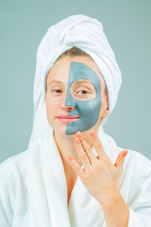 Spa Clay Mask. Beautiful young woman with clay facial mask. Skincare and beauty Concept.
